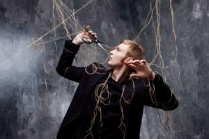 Мужчина с ножницами разрезает верёвки