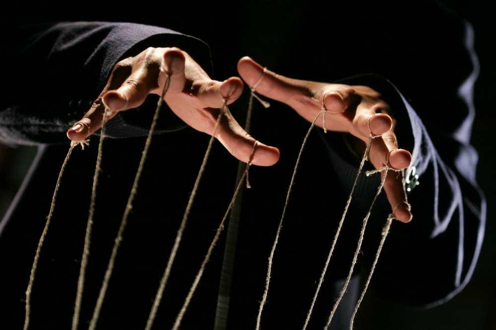 Руки человека, к которым привязаны верёвочки