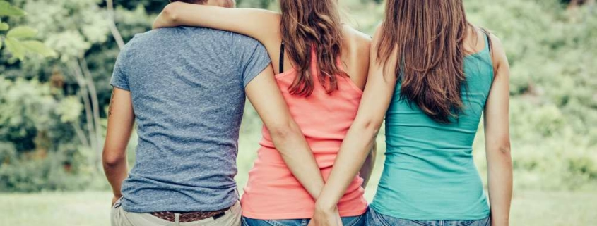 Парень и девушка обнимаются, а ещё одна девушка рядом держит парня за руку
