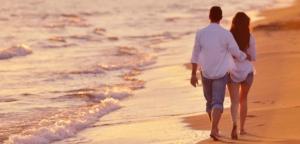 Влюблённая пара гуляет по пляжу