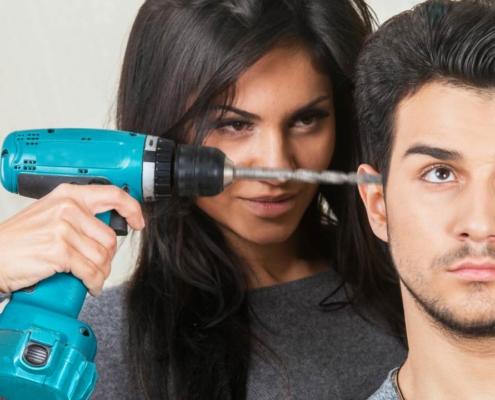 Женщина сверлит мужчину дрелью в ухо