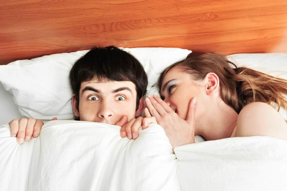 Мужчина и женщина шепчутся в постели, мужчина удивляется