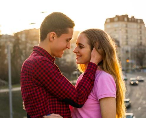 парень обнимает девушку за шею