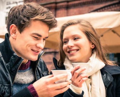 парень разговаривает с девушкой и держит чашечку кофе