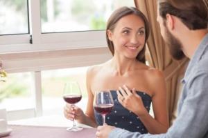 Девушка и мужчина в кафе пьют вино