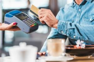 Мужчина платит картой в кафе