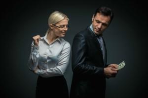 Мужчина держит деньги, а девушка подглядывает