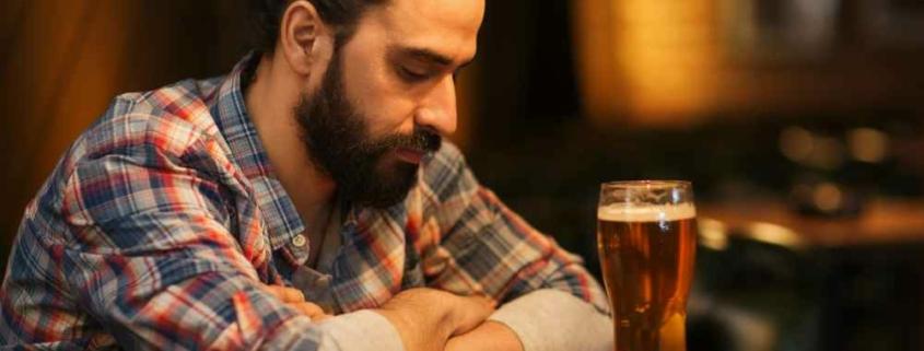 Одинокий мужчина в баре с бокалом пива