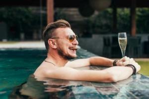 Мужчина с сигарой и бокалом вина в бассейне