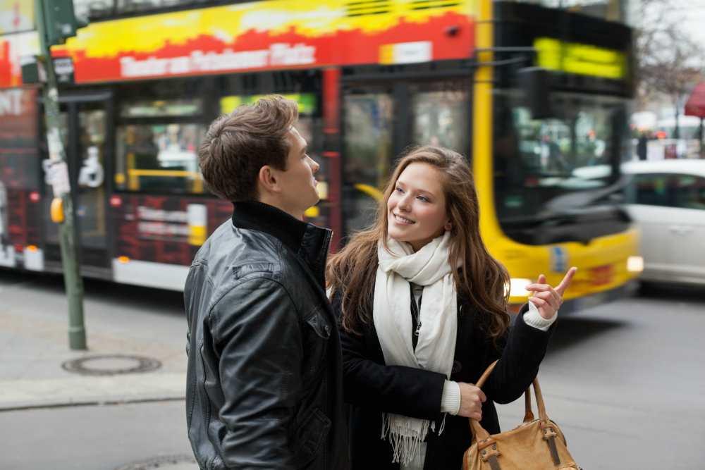 Парень и девушка болтают на улице мимо едет автобус