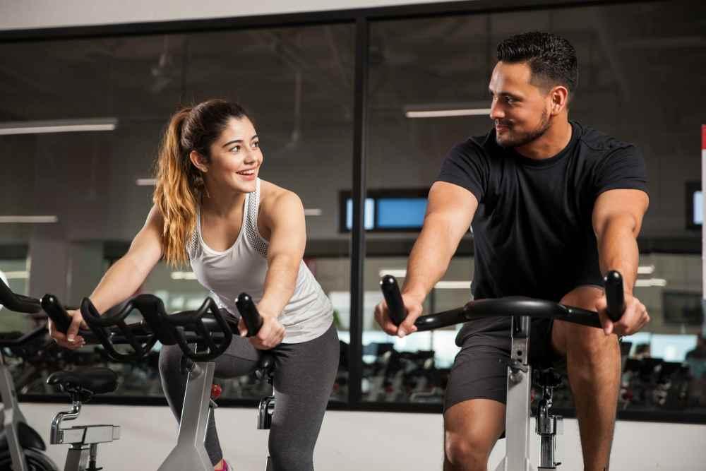 Девушка с парнем в тренажёрном зале на велотренажёрах