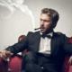 Мужчина с сигарой и стаканом виски в кресле