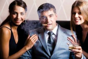 мужчина с двумя девушками и сигарой