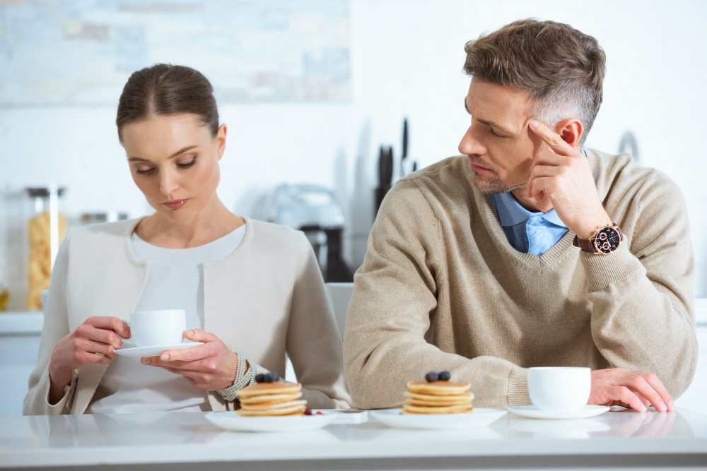 Мужчина и женщина за столом пьют кофе