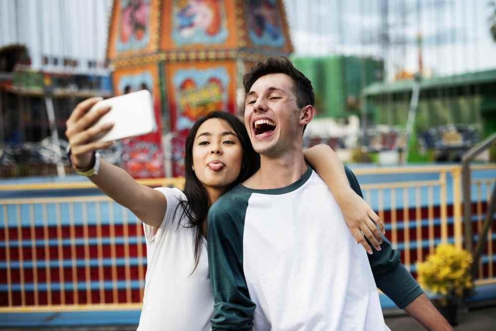 Парень и девушка в парке аттракционов делают селфи