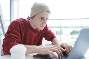 Парень пишет на компьютере у окна