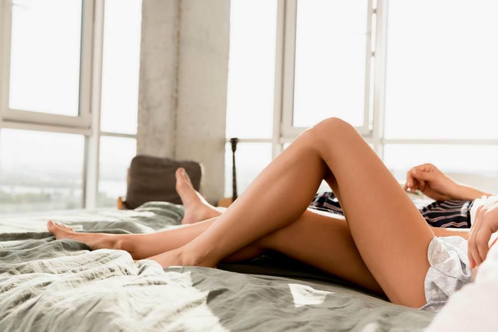 Ноги парня и девушки в постели