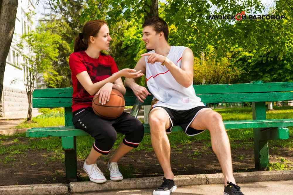 Парень и девушка разговаривают на скамейке