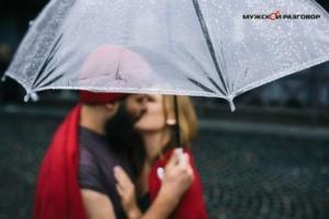 Парень и девушка целуются под зонтом
