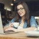 Девушка с ноутбуком пьет кофе