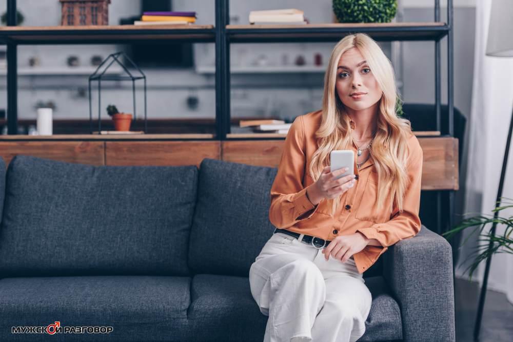 Девушка с телефоном сидит на диване