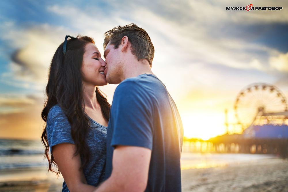 Молодая пара целуется на фоне колеса обозрения