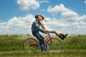 Парень везёт девушку на велосипеде по полю